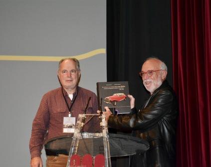Ο Βύρων Ρηγινός προσφέρει αναμνηστικό βιβλίιο στον διοργανωτή της εκδήλωσης Αχιλλέα Χουρσογλου
